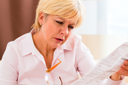 Velha mulher lendo bula medicamento em casa com