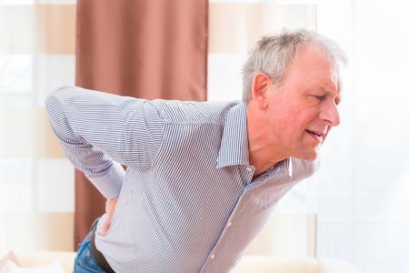 dolor de espalda: Viejo hombre que sostiene la espalda a causa de la lumbalgia