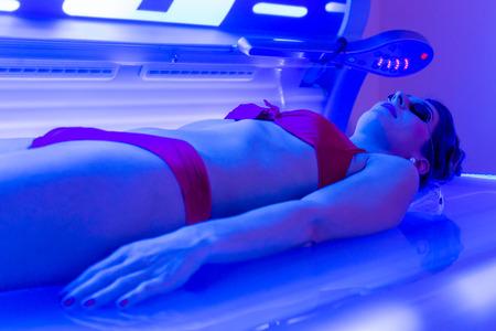 solarium: Woman in bikini tanning in wellness spa solarium
