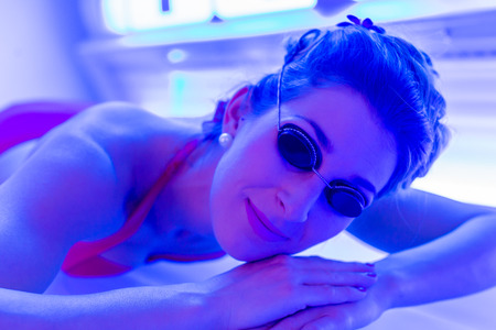 sunbed: Woman in bikini tanning in wellness spa solarium