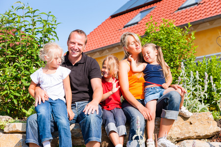 young family in front of home or house with three children sitting in the sun