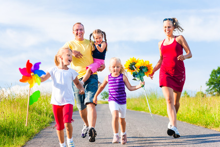 Family with three kids running down a hill in summer photo
