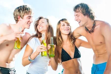 Grupo de personas muy hermosas que celebran en la playa en el verano de sus vidas photo