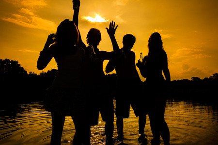 People feeling free in the sunset having a summer party in the water photo