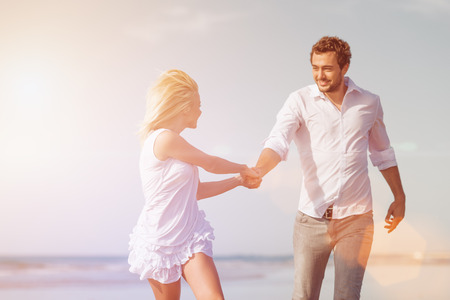 sunlit: Couple on beach in white clothing running down on vacation or honeymoon Stock Photo