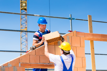 site: Two Bricklayer or builder or worker build or bricklaying or laying a stone or brick wall on construction or building site