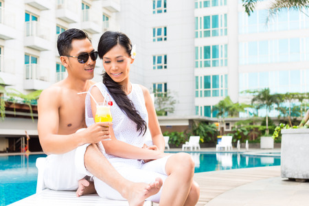 Asian couple sitting by hotel swimming pool photo