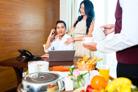 Asian room service waiter serving breakfast in hotel room photo