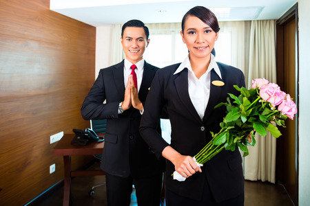 Portrait of hotel staff greeting with flowers
