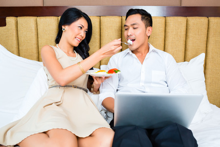 Couple sitting and eating in bed Stock Photo