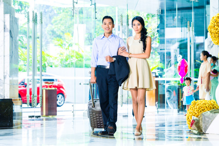 Asian couple arriving in hotel lobby Stock Photo