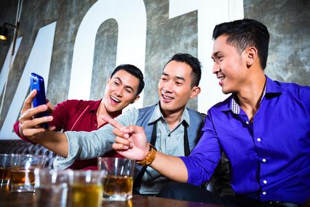 멋진 나이트 클럽에서 자신의 휴대 또는 휴대 전화로 사진 또는 selfies을 복용 젊은 친구의 아시아 파티 사람들의 그룹