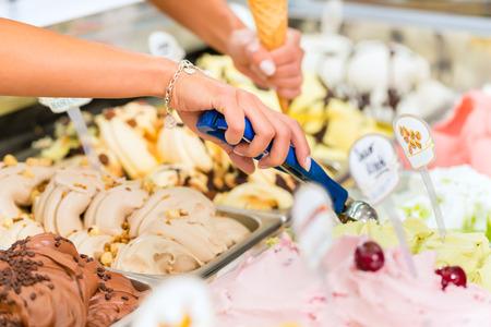 helados: Vendedora joven en una heladería tiene una bola de helado