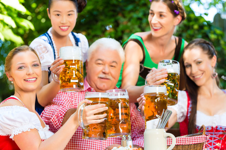 In Beer garden - friends in Tracht, Dirndl and Lederhosen drinking a fresh beer in Bavaria, Germany Stock Photo - 28394172