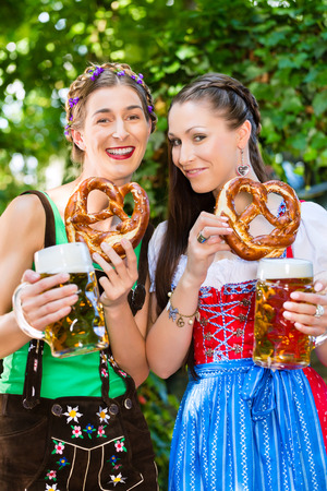 In Beer garden - female friends in Tracht, and Dirndl drinking a fresh beer and eating pretzel in Bavaria, Germany Stock Photo - 28394173