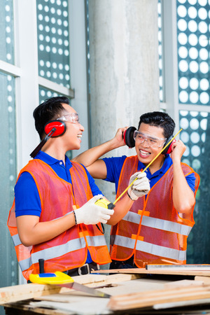 Asian Indonesian builder or craftsman and supervisor with ear or hearing protection and glasses on a tower building or construction site photo