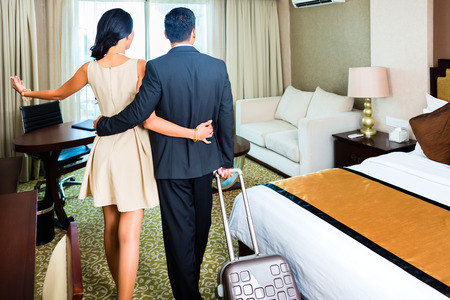 Rear view of couple arriving to hotel room photo