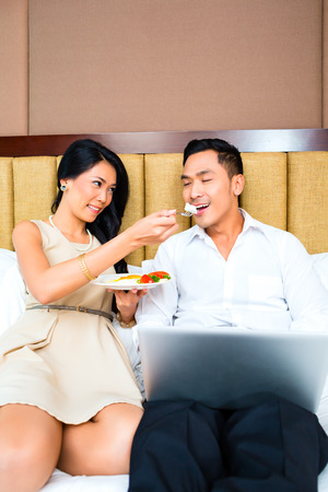 Couple sitting and eating in bed photo