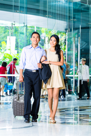 arriving: Asian couple arriving in hotel lobby Stock Photo