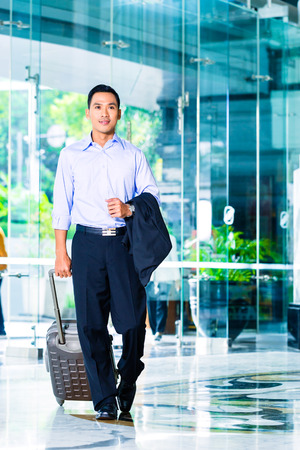 Asian man walking and pulling suitcase in hotel lobby photo