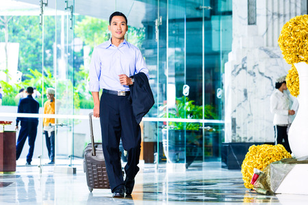 Asian man pulling suitcase in hotel lobby photo