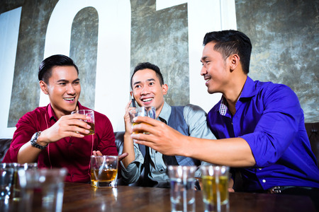 Asian young and handsome group of party people or male friends looking at smart mobile phone in fancy night club Stock Photo