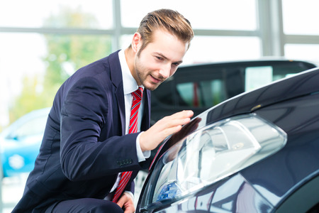 used car: Seller or car salesman in car dealership presenting the reflecting car paint of his new and used cars in the showroom Stock Photo