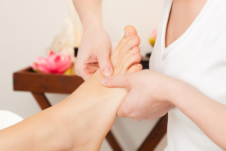 reflexology: Feet receiving a massage in a spa setting  Stock Photo
