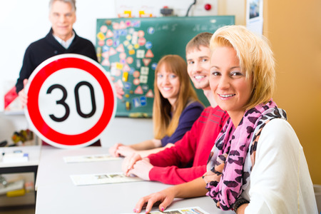 theoretical: Driving school - driving instructor and student drivers with a tempo thirty Road sign, in the background are traffic signs Stock Photo