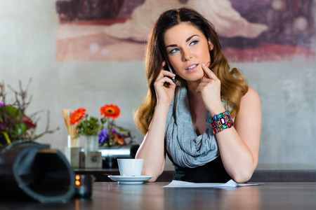 likeable: Young woman on the phone in a cafe or restaurant, she discusses some documents