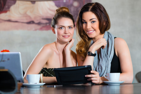 Young women or colleagues sitting in a cafe or restaurant, and looking on the Tablet Computer photo