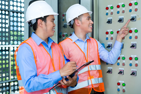 Asian Indonesian Technician or electrician making function test on Panel or switchbox for the control of air conditioners on construction site or in factory for acceptance photo