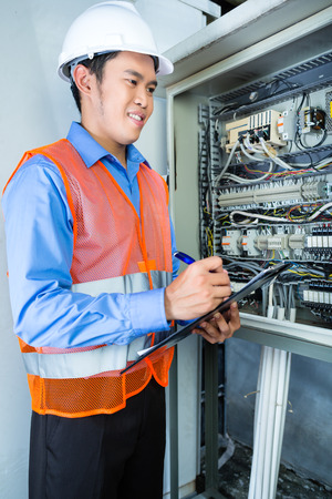 acceptance: Asian Indonesian Technician or electrician making function test on breaker box or switchbox with power lines on construction site or in factory for acceptance