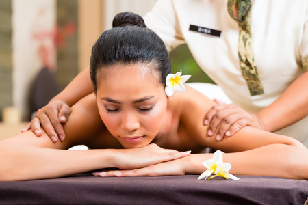 body massage: Indonesian Asian woman in wellness beauty day spa having aroma therapy massage with essential oil, looking relaxed
