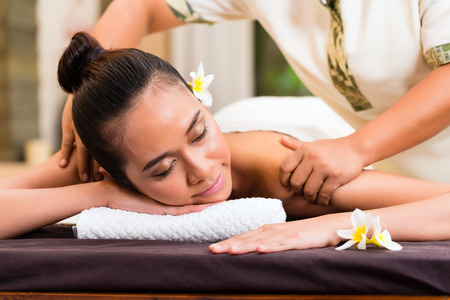 oriental massage: Indonesian Asian woman in wellness beauty day spa having aroma therapy massage with essential oil, looking relaxed