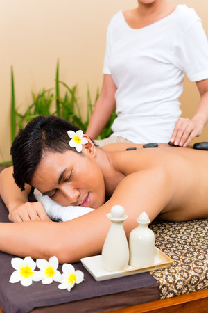 Indonesian Asian man in wellness beauty day spa having hot stone massage or treatment, looking relaxed photo