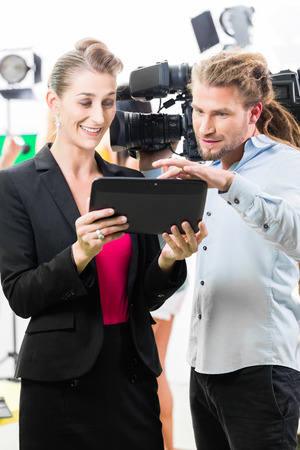 group direction: Team discussion or Director giving cameraman scene direction on set of a video production for TV or News