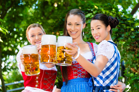 In Beer garden - female friends in Tracht, and Dirndl in Bavaria, Germany Stock Photo - 28531112