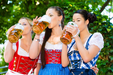 In Beer garden - female friends in Tracht, and Dirndl in Bavaria, Germany photo