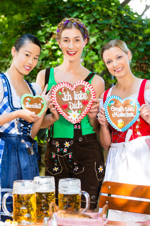 Young women in traditional Bavarian clothes or tracht with a gingerbread souvenir heart in beergarden on Oktoberfest Stock Photo - 28531114