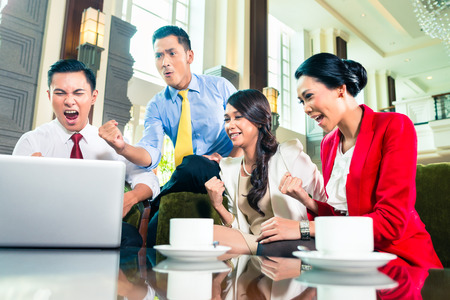 Asian Businesspeople watching a laptop and cheering photo