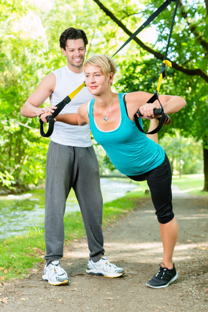 Fitness woman exercising with suspension trainer and personal sport trainer in City Park under summer trees photo