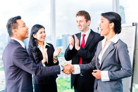 フリップチャートの前で手を振ってアジアのビジネスマン 写真素材