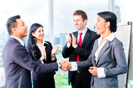 deals: Asian Businesspeople shaking hands in front of flipchart Stock Photo