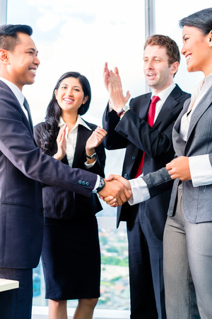 caucasians: Asian Businesspeople shaking hands in office