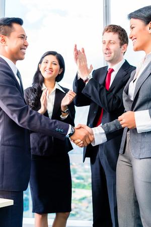 hombre caucasico: Los empresarios asi�ticos que sacuden las manos en la oficina