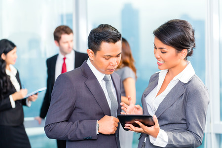 Portrait of Asian businesspeople looking at tablet together photo