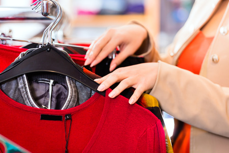 clearance sale: Woman choosing clothes on clothes rail in boutique or fashion store Stock Photo
