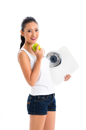 Young Asian woman losing weight by living healthy and eating fruits Imagens