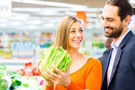 Couple selecting vegetables while grocery shopping in supermarket  photo